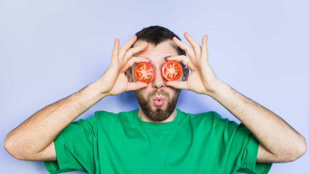 homem comendo tomate